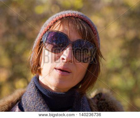 portrait of a pretty woman in the autumn park in solar sunny day