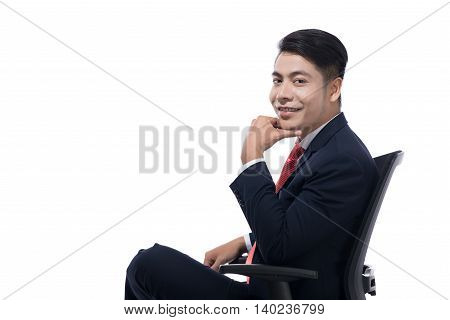 Young businessman sitting in swivel chair over white background thinking