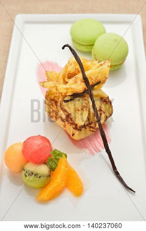 Fried potato with cream and fruit cake on white plate in restaurant