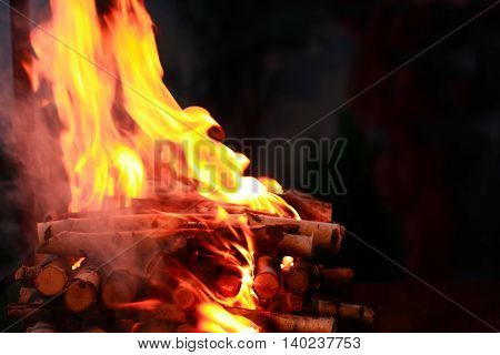Flame background. Firewood closeup burning on dark background