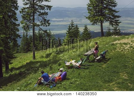 Poiana Brasov, Romania - June 26 2016: People relax in their sunbeds and picnic and enjoy the view on weekends or during summer vacation near Postavaru Chalet up in the Postavaru Mountain.