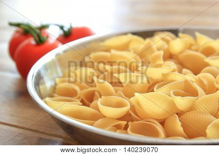 Dry Conchiglie Pasta Shells In A Stainless Steel Bowl With Vine Tomatoes In The Blurred Background