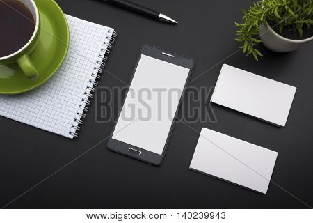 Business card blank, smartphone or tablet pc, flower and pen at office desk table top view. Corporate stationery branding mock-up.