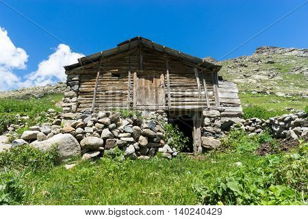 View Of A Wooden Mountain Cabin With Mountains In The Background