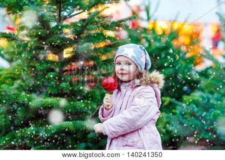 Cute little kid girl eating crystalized sugared apple on German Christmas market. Happy child in winter clothes  with lights on background. Kid looking at the camera. Family, tradition, holiday concept