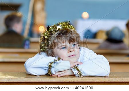 Adorable toddler, little kid boy playing an angel in Christmas story in a church. Happy adorable blond child with lights and xmas tree on background.