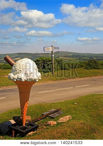 Large ice cream cone in the Dartmoor national park with road signage in the background