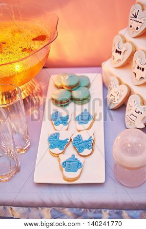 sweet table with cookies and a drink at a birthday party.