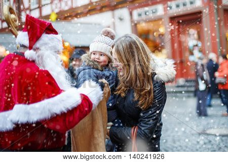 Cute toddler girl with mother on Christmas market. Funny happy kid taking gift from bag of Santa Claus. holidays, christmas, childhood and people concept. Happy family during snowfall on winter day.