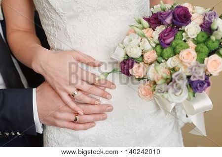 hands of bride and groom with rings on the waist of the bride and the bridal bouquet.