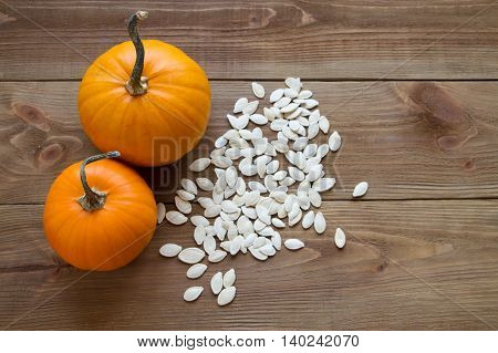 small ripe pumpkin with seeds on a wooden background