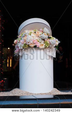 bouquet of white and pink flowers in the white cylinder.
