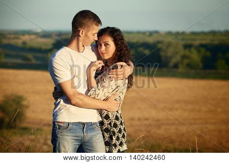 young couple posing high on country outdoor at sunset, romantic people concept, wheaten field and forest on background, summer season