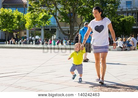 Baby boy walking with his mother on sunny promenade