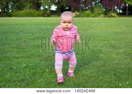 Little baby girl walking in the park