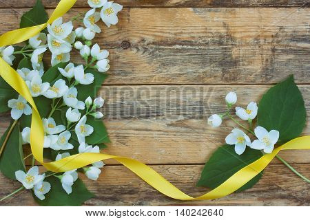 branches delicate fragrant jasmine and yellow silk ribbon on a wooden table