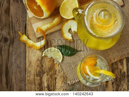 jug and glass homemade lemonade orange lemon stands on an old rustic wooden table