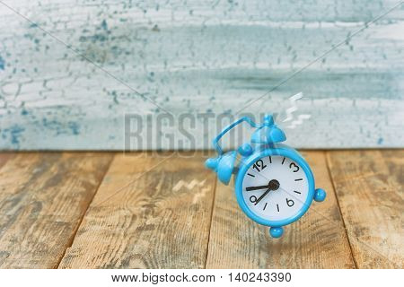 Blue retro alarm clock ringing old wooden table retro style