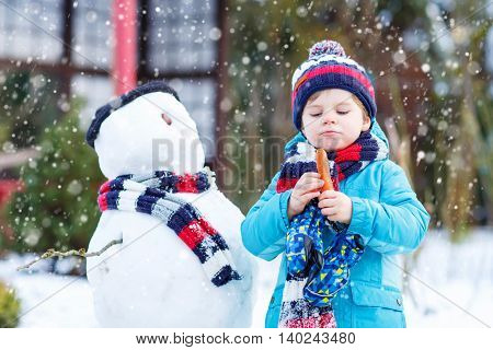 Adorable little toddler boy making a snowman and eating carrot, playing and having fun with snow, outdoors  on cold day. Active outdoors leisure with kids in winter.