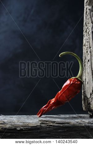dried chili peppers on wood against a dark background