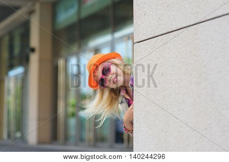 Adorable happy child in sunglasses and orange hat. Shop windows in the background. Girl peeking around the corner. Blond hair fluttering in the wind.
