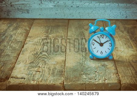 Blue retro alarm clock standing on old wooden table vintage toned