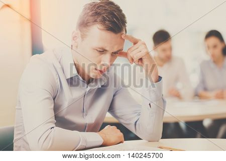 Deadline today. Businessman sitting sad and solving problem in office, his co-workers discussing business matters in the background