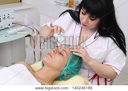 People, beauty, spa, cosmetology and technology concept - close up of beautiful young woman lying with closed eyes having face massage by massager in spa.
