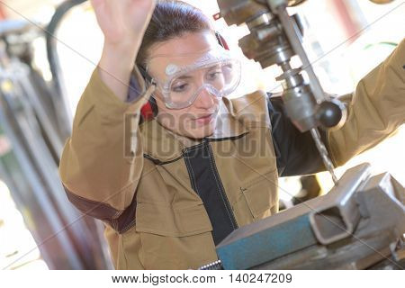 beautiful brunette factory worker drilling a piece