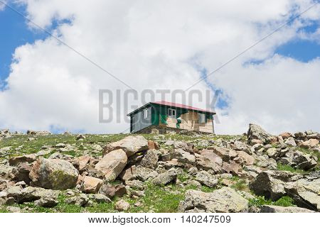 View Of A Wooden Mountain Cabin With Blue Sky In The Background