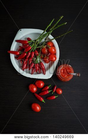 Tomato ketchup sauce with cherry tomatoes and mini red hot chili peppers in a small glass jar with a spoon on dark wooden background. Homemade tomato sauce and fresh tomatoes. Top view.