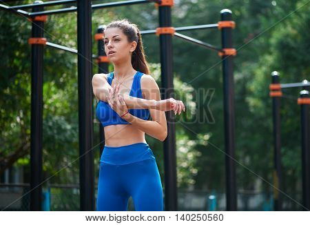 Athletic woman warming up before her morning workout at outdoor workot zone. healthy lifestyle concept