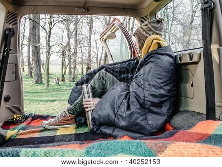 Woman in sleeping bag resting in car interior