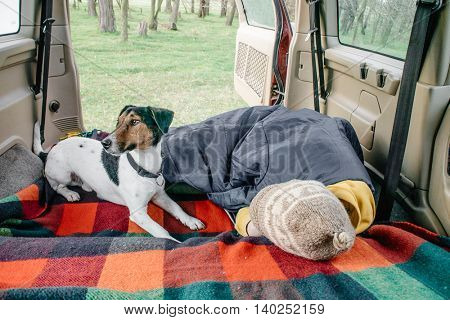 Woman and her dog resting in car interior