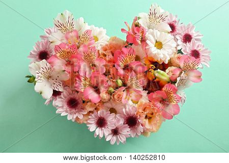 Composition of beautiful flowers in a heart shape on turquoise background