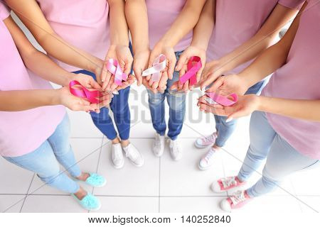 Female hands holding pink ribbons. Breast cancer concept