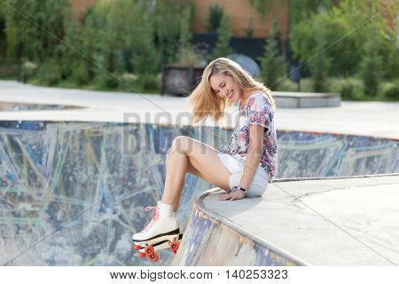 Pretty young woman enjoying the quality time with a pair of vintage roller skates.