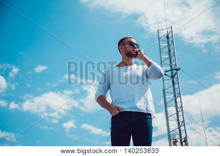 Man talking on the phone on the roof. Mobile antenna. Sky.