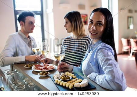 Portrait of happy young woman having food with friends at bar counter