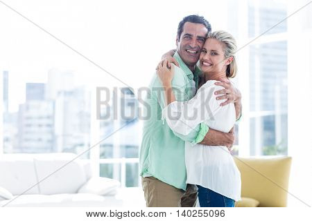 Portrait of mid adult smiling couple hugging at home