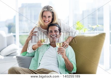 Portrait of mid adult couple holding winglasses at home