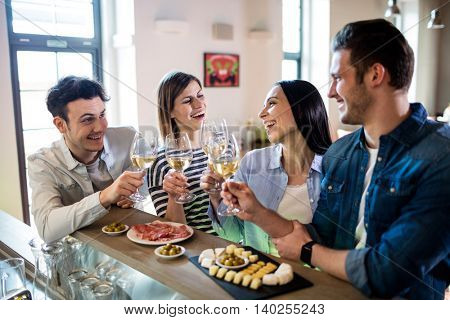 Happy young friends enjoying wine and food at bar counter