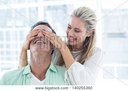 Mid adult romantic woman covering eyes of man at home