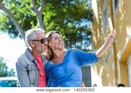 Smiling mature couple taking selfie in city