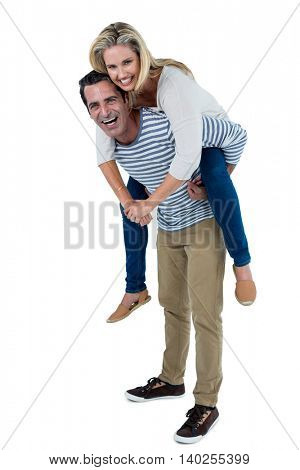 Happy man carrying woman piggyback against white background