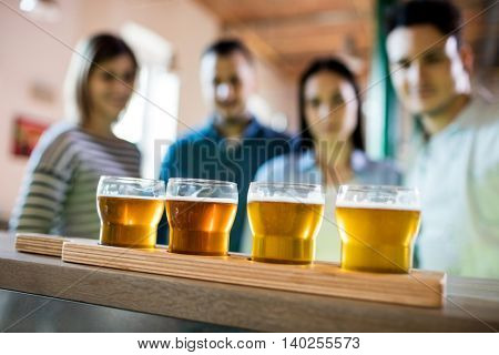 Friends standing in front of beer sampler on counter at bar