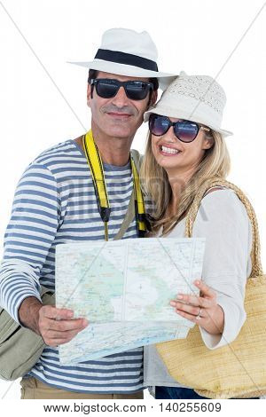 Portrait of mid adult couple holding map against white background