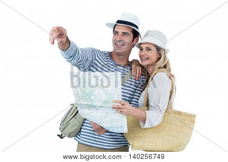 Mid adult couple pointing while holding map against white background