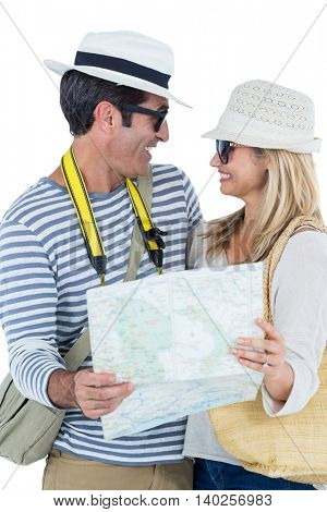 Happy couple looking at each other while holding map against white background