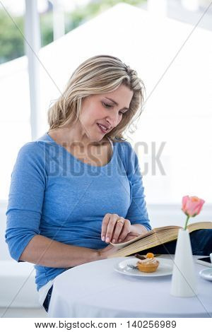 Smiling mature woman reading book while sitting at restaurant